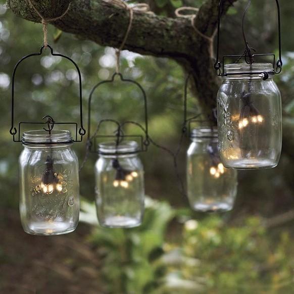 Bocaux avec des LED suspendus dans un jardin.
