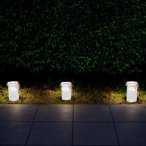 Lumières LED en bocal sur le bord d'un chemin de jardin.