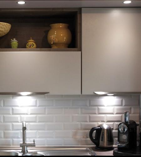 Photo d'une cuisine moderne avec un plan de travail éclairé par des LED blanc neutre.