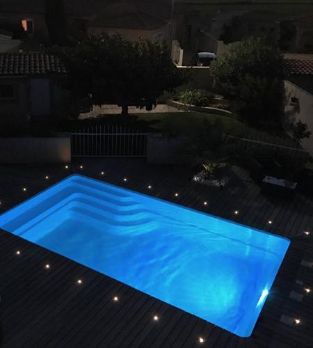 Piscine privée entourée de petits spots LED.